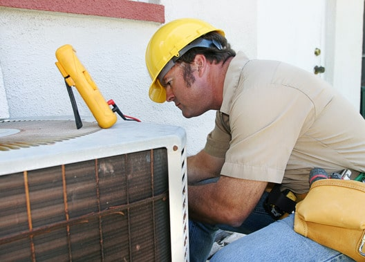 HVAC Tech performing repair on an air conditioner unit.